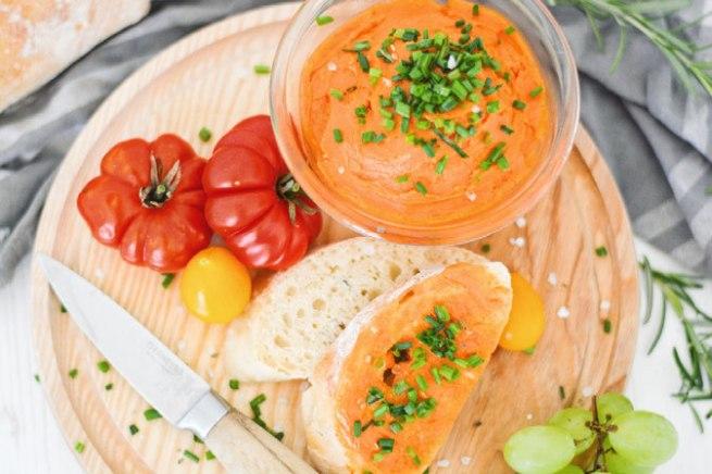 Auf diesem Bild siehst du eine vegane Tomaten - Knoblauchbutter von oben fotografiert. Auf der Knoblauchbutter ist frisch geschnittener Schnittlauch.