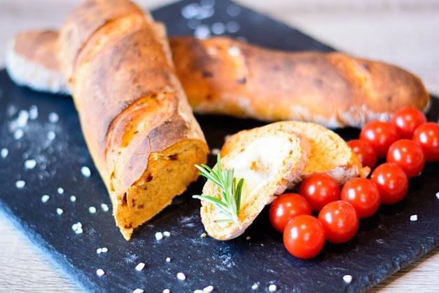 Auf diesem Bild ist ein Tomatenbaguette zu sehen. Neben dem Baguette liegen frische Tomaten und Rosmarin.