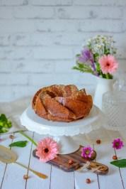 Zuckerfreier Schoko - Nuss Gugelhupf von vorne fotografiert. Im Hintergrund steht ein großer Blumenstrauß. Neben dem Kuchen liegt ein altern Tortenheber.