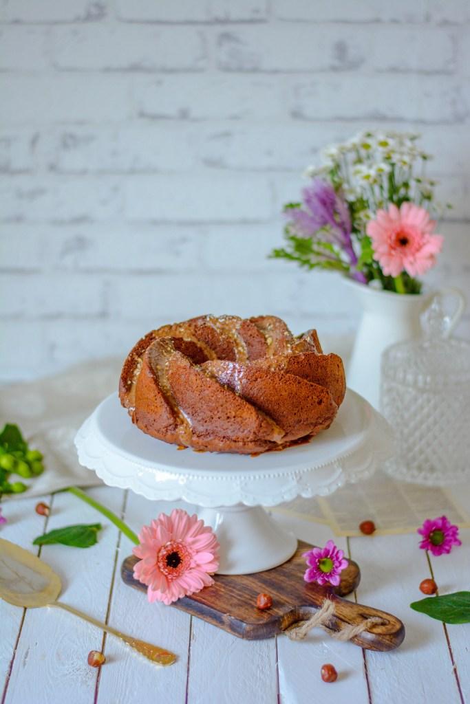 Schoko - Nuss Gugelhupf fotografiert umgeben von Blumen und einem Vintage Tortenheber und auf alten Holzdielen.