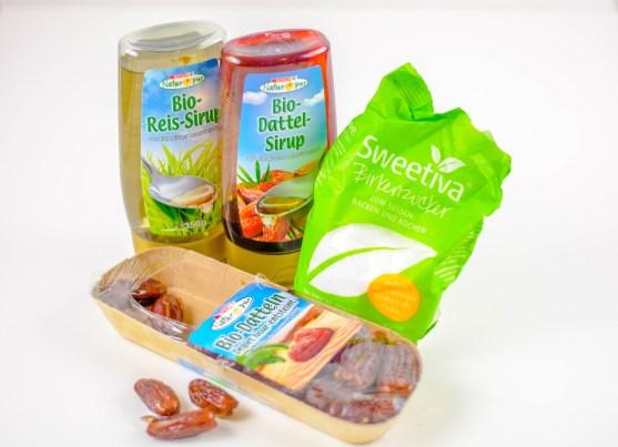 Auf diesem Bild sind unterschiedliche Zuckeralternativen zu sehen. Im Vordergrund liegen Datteln, dahinter steht ein Dattelsirup, Reissirup und Birkenzucker.