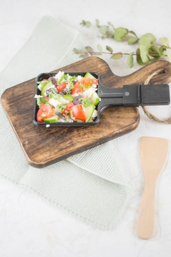 Raceltte Pfännchen mit griechischem Salat auf einem kleinen Holzbrett. Im Hintergrund sieht man ein türkises Geschirrtuch und Eukalyptusblätter.