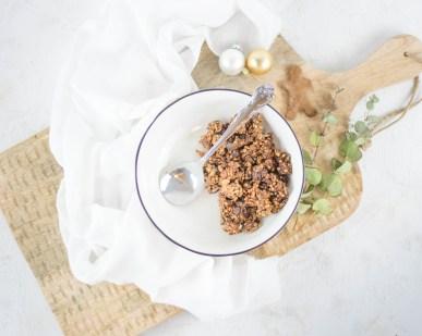 Auf diesem Bild ist ein zuckerfreies Lebkuchen Granola zu sehen. Das Lebkuchen Granola wurde von oben fotografiert. Das Granola liegt einer einer weißen Müslischüssel, welche auf einem großen Holzbrett steht. Daneben liegen kleine Christbaumkugeln, ein weißes Geschirrtuch und ein Lebkuchenplätzchen.