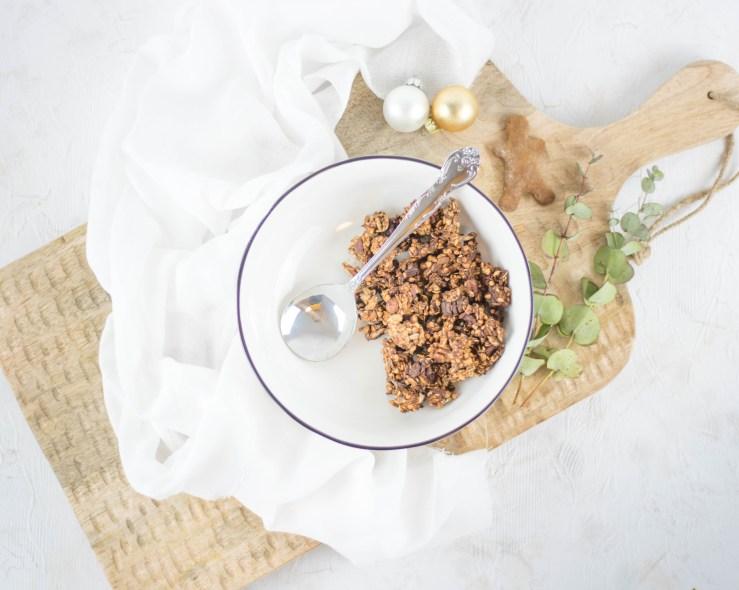 Hier liegt zuckerfreies Lebkuchen Granola in einer schönen Müslischale. Die Schale steht auf einem großen Holzbrett gemeinsam mit einem Lebkuchenmann, einem Eukalyptuszweig und zwei kleinen Christbaumkugeln.
