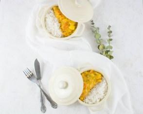 Auf diesem Bild ist ein Kürbis Curry zu sehen. Das Curry wurde von oben fotografiert. Daneben liegt ein weißes Geschirrtuch und Eukalyptusblätter.