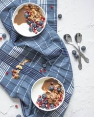 Hier ist ein zuckerfreies Kokos - Granola auf einem Naturjoghurt mit frischen Beeren und etwas Nussmus zu sehen. Die Müslischüsseln stehen auf einem dunkelblauen Geschirrtuch und daneben liegen zwei silberne Löffel.