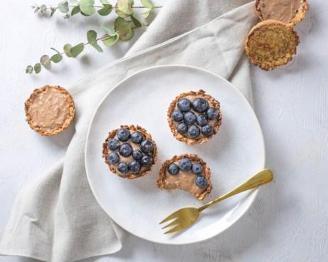 Zuckerfreie Haferflocken Tartes mit Nutella - Quarkcreme auf einem weißen Teller. Daneben liegt ein braunes Geschirrtuch und zwei Eukalyptuszweige.