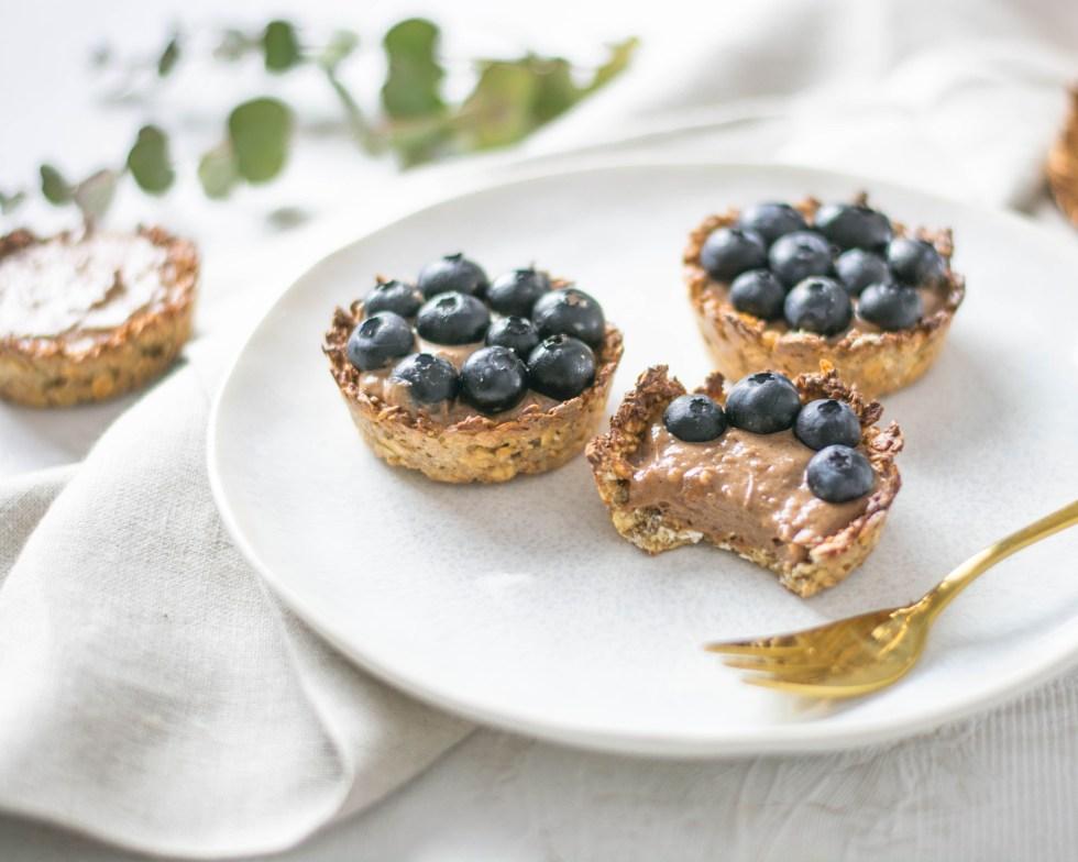 Auf diesem Bild sind zuckerfreie Tartes mit Nutella - Quarkcreme zu sehen. Sie liegen auf einem weißen Teller, gemeinsam mit einer goldenen Gabel.