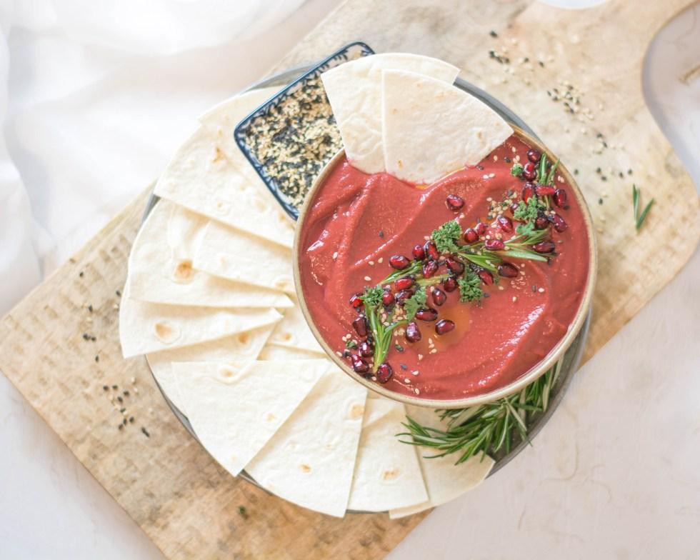 Rote Beete Hummus von oben fotografiert! Der Hummus ist in einer Schüssel angerichtet und wurde mit Rosmarin, Petersilie, Sesam und Granatapfelkernen dekoriert.