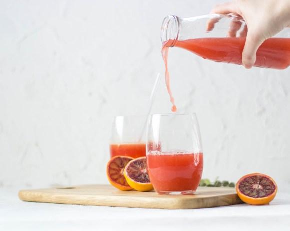 Auf dem Bild von Arbeite mit mir ist ein Blutorangensaft zu sehen. Der Saft ist in einem Glas, welches auf einem Holzbrett steht. Eine Glasflasche mit Orangensaft wird über das Glas gehalten und der Saft läuft in das Glas.