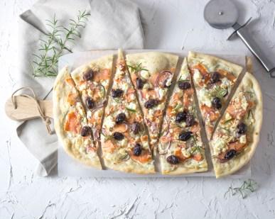 Auf diesem Bild ist ein Flammkuchen mit Räucherlachs und Oliven zu sehen. Der Flammkuchen liegt auf einem Holzbrett und wurde in Dreiecke geschnitten. Daneben liegt frischer Rosmarin und ein Pizzaroller.