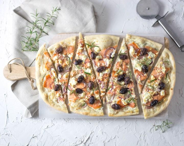 Auf dem Bild ist ein Flammkuchen mit Räucherlachs und Oliven zu sehen. Der Flammkuchen wurde in große Dreiecke geschnitten und auf einem großen Holzbrett serviert.