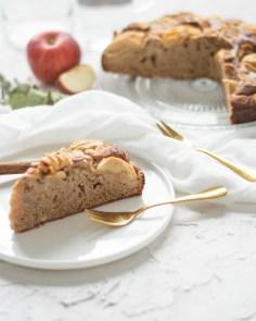 Hier ist ein frisch angeschnittener, zuckerfreier Dinkel - Apfelkuchen zu sehen. Das Kuchenstück liegt auf einem weißen Dessertteller, im Hintergrund ist der restliche Kuchen und ein angeschnittener Apfel zu sehen. Daneben liegen zwei goldene Dessertgabeln und ein weißes Geschirrtuch.