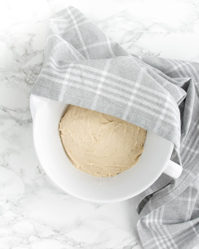 Hier wurde der Teig für mein Backrezept für Ostern von oben fotografiert. Der Teig liegt in einer weißen Schüssel, über der Schüssel liegt zur Hälfte ein graues Geschirrtuch.