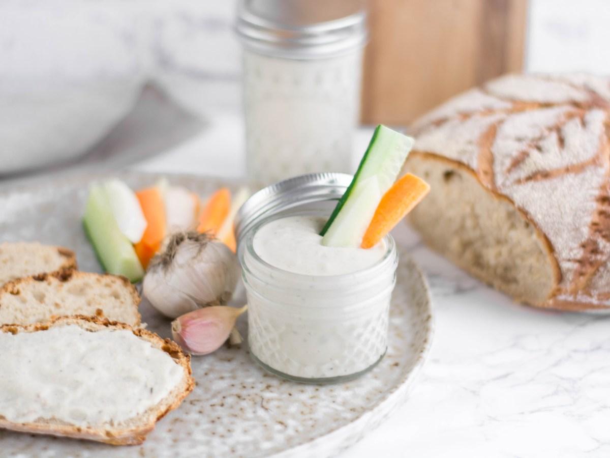 Auf diesem Bild ist ein veganer Knoblauchdip auf Cashew - Basis zu sehen. Das Bild wurde von vorne fotografiert. Im Hintergrund liegt ein frisch gebackenes Brot und daneben liegt frisch geschnittenes Gemüse.