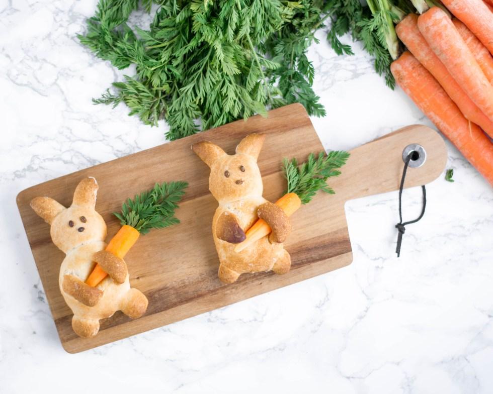 Auf diesem Bild ist ein Backrezept für herzhafte Osterhasen zu sehen. Das Bild wurde von oben fotografiert, die Osterhasen liegen auf einem Holzbrett und daneben liegen Karotten.
