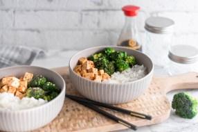 Auf diesem Bild ist ein gebratener Brokkoli mit Reis zu sehen. Der Brokkoli wurde in einer beigen Schüssel gemeinsam mit Tofu und Reis schön angerichtet. Im Hintergrund steht eine Flasche Sojasauce.