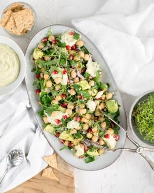 Hier ist ein schneller Kichererbsen Salat zu sehen, welcher auf einem Servierteller schön angerichtet wurde. Daneben stehen kleine Schüsseln mit den Grundzutaten.