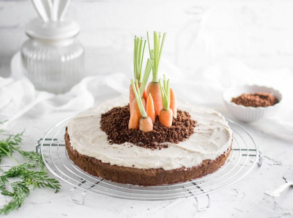 Auf diesem Bild ist eine vegane und zuckerfreie Rüebli Torte zu sehen. Der Möhren Kuchen wurde von schräg vorne fotografiert und mit Karotten dekoriert.
