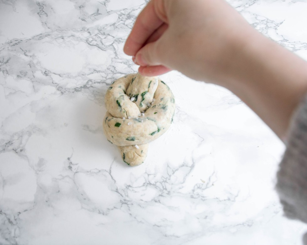 Auf dem Bild sieht man den Teigling, wie er mit groben Salz bestreut wird. Das geschieht kurz bevor die Brötchen in den Backofen kommen.