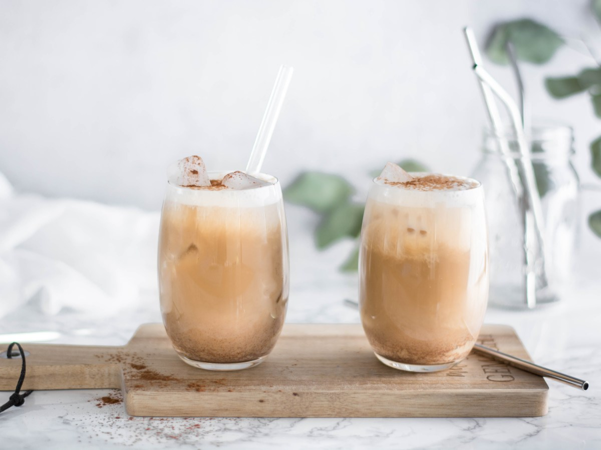 Auf diesem Bild kannst du zwei Gläser mit Eiskaffee ohne Reue sehen. Der Eiskaffee wurde von vorne fotografiert und mit Eiswürfeln und Kakaopulver dekoriert. Im Hintergrund sind Eukalyptusblätter zu sehen und ein Glas mit Metallstrohhalmen.
