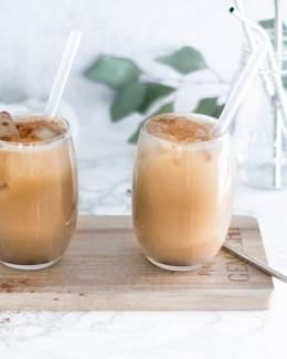 Hier kannst du ein iced Coffee Rezept für einen Eiskaffee ohne Reue sehen. Der Eiskaffee steht auf einem Holztablett und im Hintergrund sind Eukalyptusblätter zu sehen.