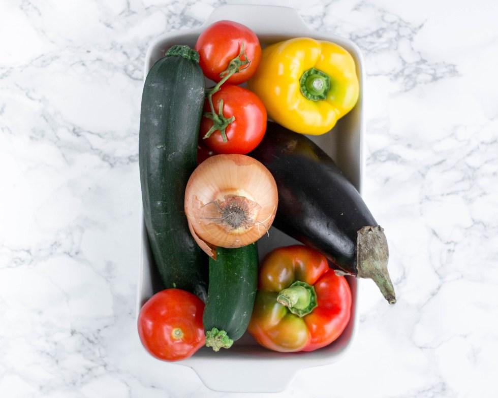 Hier kannst du jede Menge Gemüse sehen, dass du für ein Ratatouille benötigst. Es sind Zucchini, Auberginen, Paprika, Tomaten und Zwiebeln zu sehen.