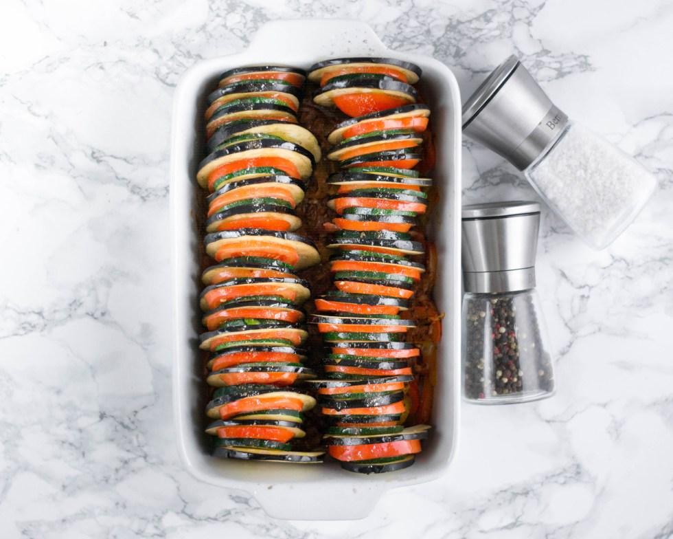 Am letzten Bild der Bild - für - Bild - Schrittanleitung ist das fertige aber noch ungebackene Ratatouille zu sehen. Das Gemüse wurde mit Olivenöl beträufelt und kommt nun in den Ofen.