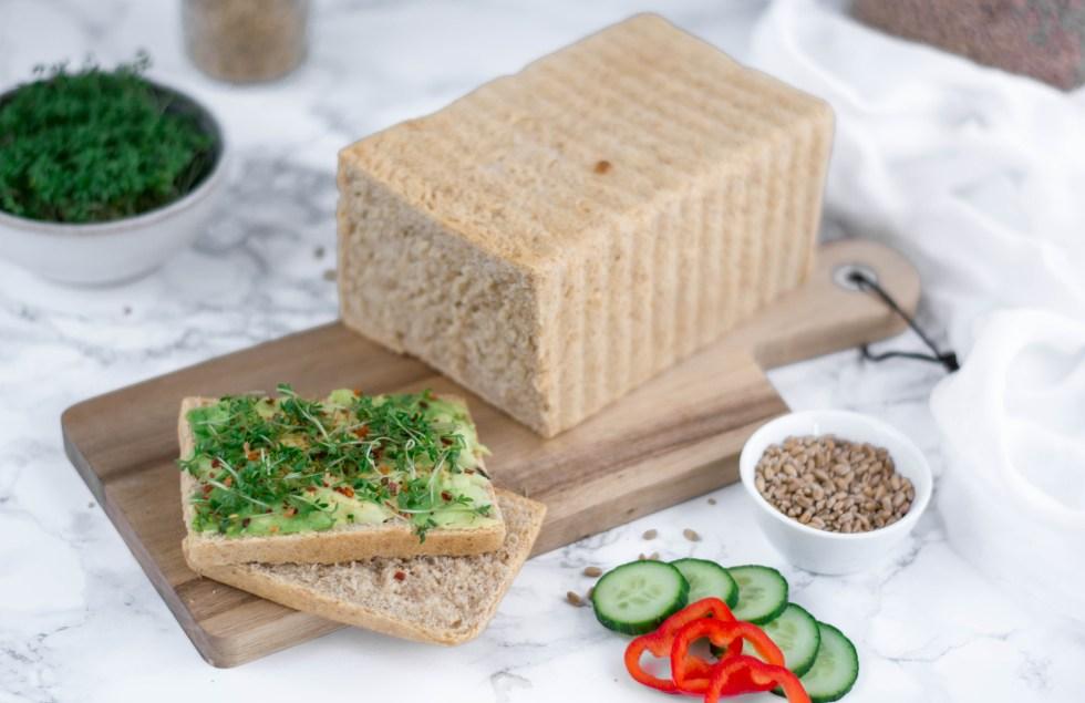 Toastbrot selber machen ist einfacher als du denkst und kannst du hier auf diesem Bild sehen. Dieses Toastbrot wurde mit viel Liebe selbstgebacken und besteht aus Dinkelmehl und Dinkelvollkornmehl. Im Hintergrund sieht man frische Kresse, Getreide und frisches Gemüse.