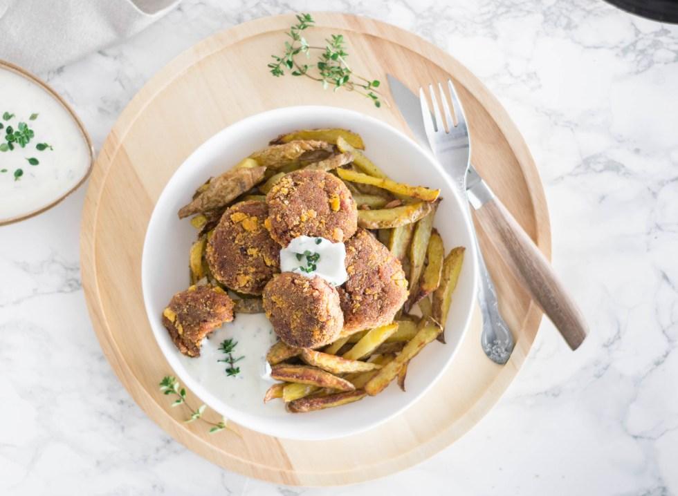 Auf diesem Bild sind vegane Frikadellen aus Kidneybohnen zu sehen. Die Frikadellen liegen auf einem Teller mit Ofenpommes. Das weiße Teller steht auf einem Holzbrett und daneben eine Schüssel mit einer Schnittlauchsoße.