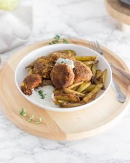 Hier sind vegane Frikadellen aus Kidneybohnen zu sehen. Die Frikadellen liegen auf einem Teller mit Ofenpommes. Das weiße Teller steht auf einem Holzbrett und daneben eine Schüssel mit einer Schnittlauchsoße.