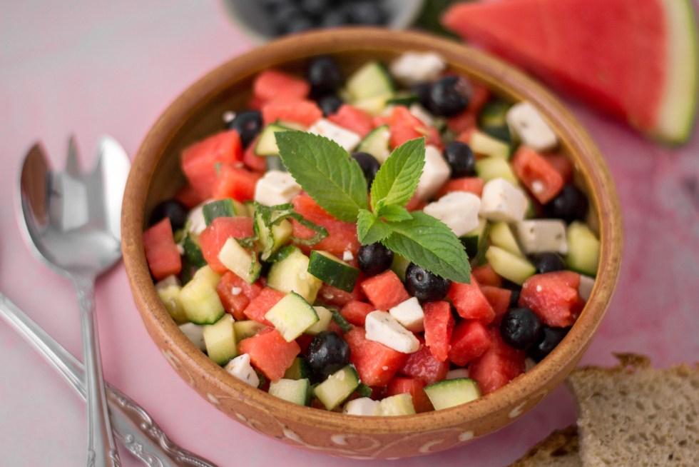 Auf diesem Bild ist ein sommerlicher Wassermelonen - Feta Salat zu sehen. Der Salat wurde in einer handgetöpferten Schüssel angerichtet und steht auf einem pinken Marmor.