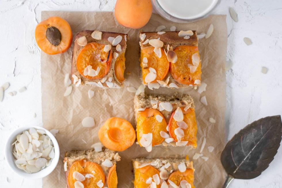Auf diesem Bild ist ein zuckerfreier und veganer Marillenkuchen zu sehen. Der Marillenkuchen liegt auf einem braunen Backpapier und wurde mit Mandelblättchen bestreut.