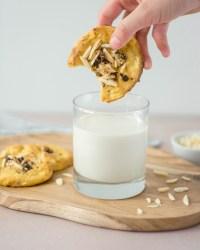 Hier sind zuckerfreie Apfel - Hafer Cookies zu sehen, die von vorne fotografiert wurden. Einer der Kekse wird gerade in ein Glas mit Milch getunkt. Das Milchglas steht auf einem alten Holzbrett.