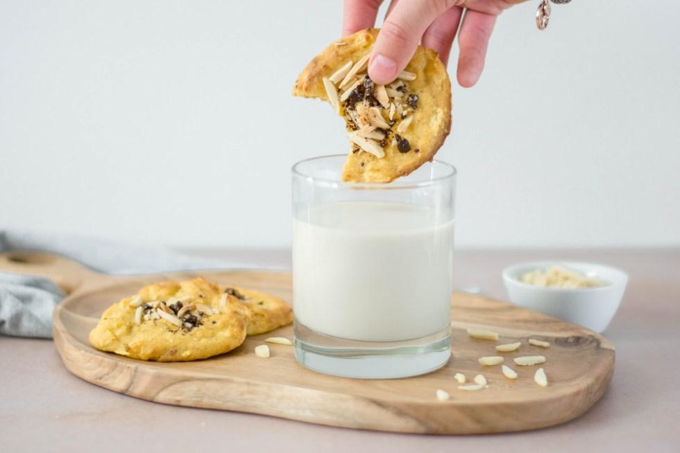 Auf diesem Bild sind zuckerfreie Apfel - Hafer Cookies zu sehen, die von vorne fotografiert wurden. Einer der Kekse wird gerade in ein Glas mit Milch getunkt. Das Milchglas steht auf einem alten Holzbrett.