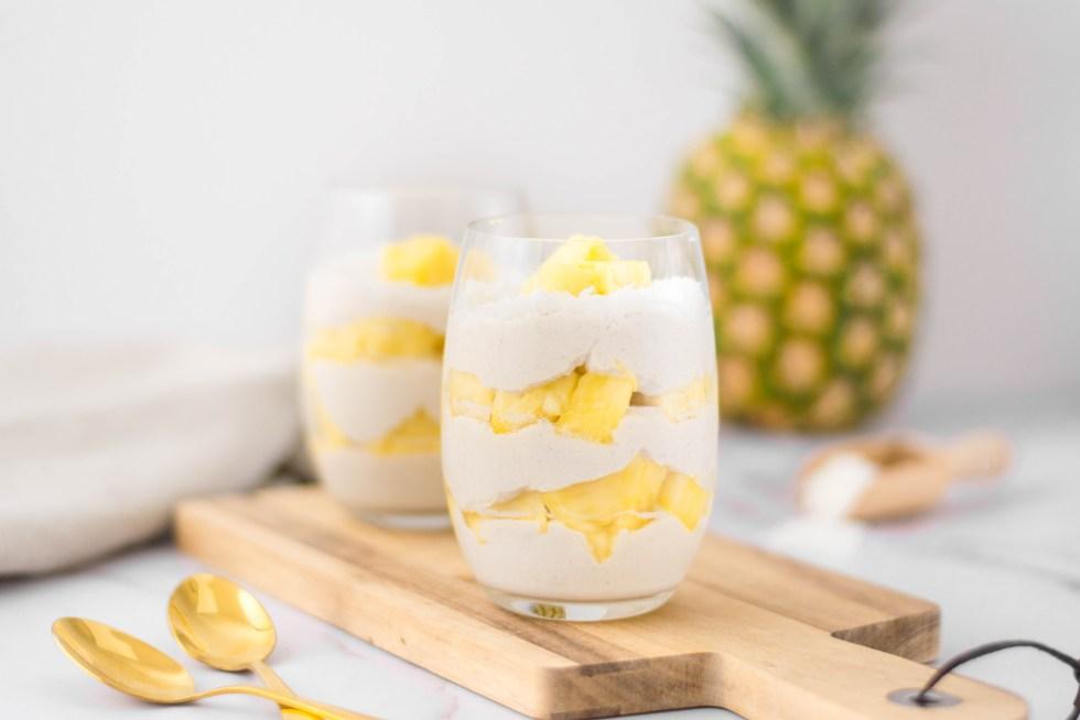 Auf diesem Bild ist ein veganes Pina Colada Dessert im Glas zu sehen. Die zwei Dessert Gläser stehen auf einem Holzbrett und im Hintergrund steht eine Ananas.