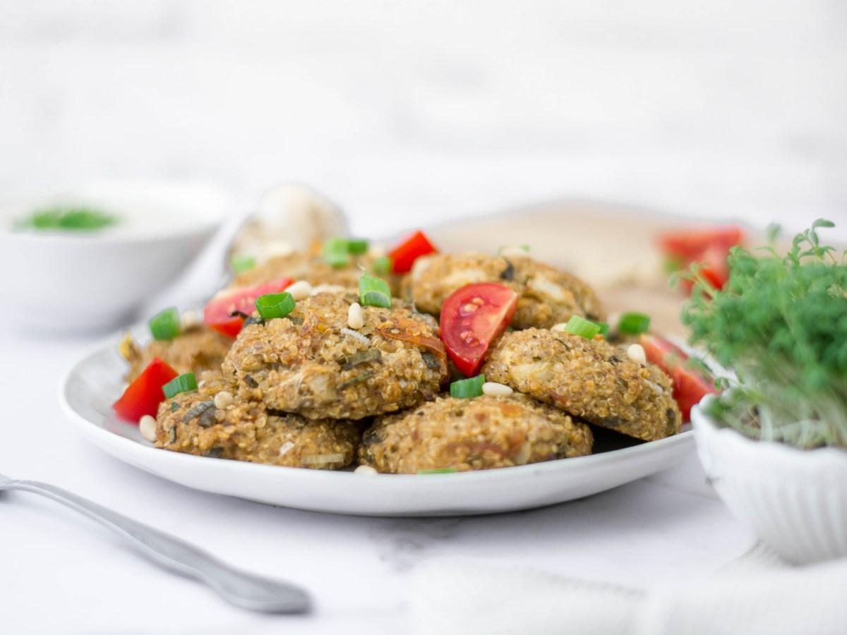 Auf diesem Bild sind mediterrane Quinoa Laibchen zu sehen, die auf einem Teller mit Frühlingszwiebeln, Tomaten und Pinienkernen angerichtet wurden.