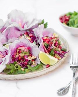 Hier ist ein schön angerichteter Hibiskusblüten Salat zu sehen. Der Salat wurde in die Hibiskusblüten eingefüllt und auf einem Teller angerichtet.