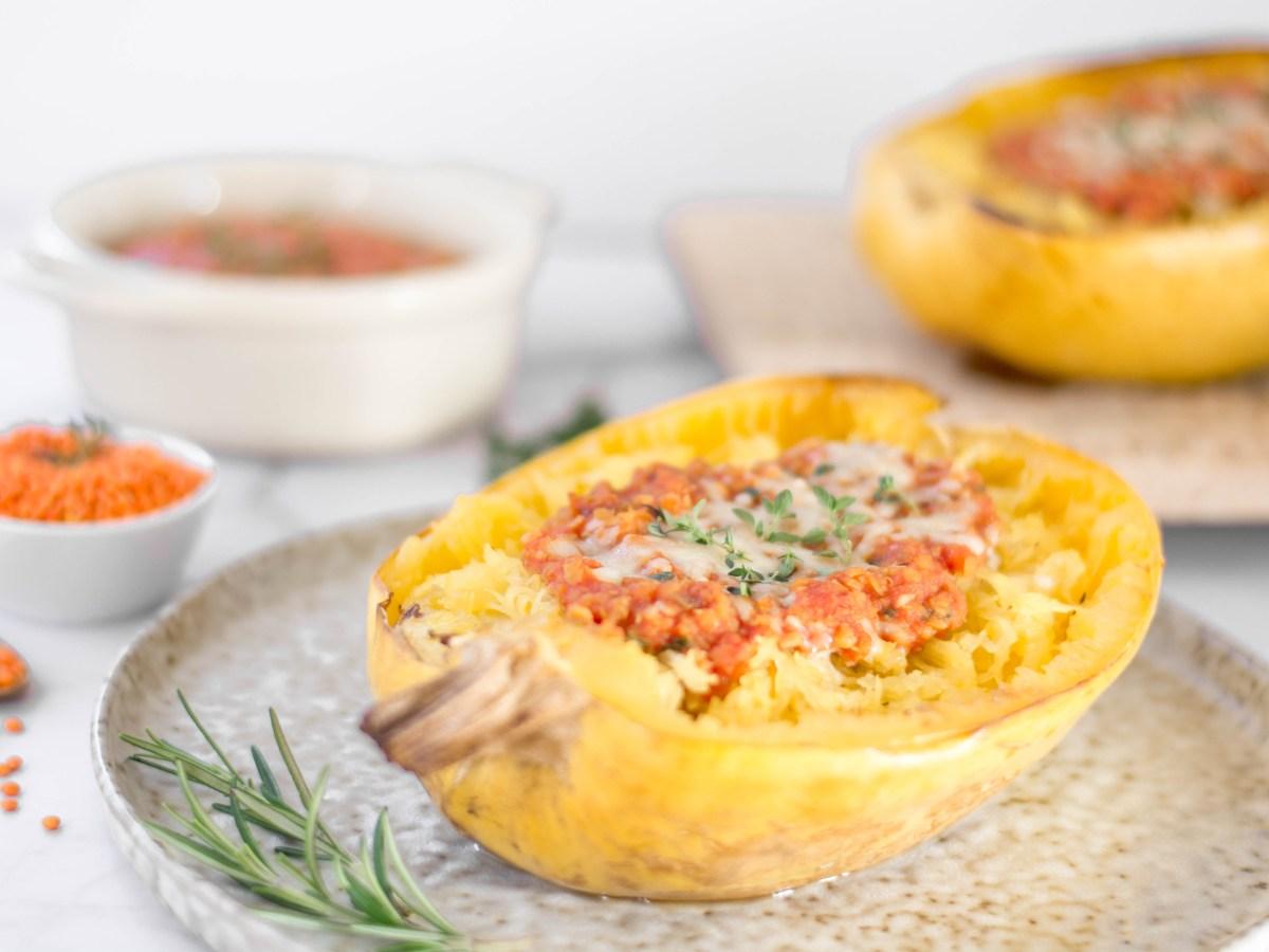 Auf diesem Bild ist ein Spaghetti Kürbis mit roter Linsen Bolognese zu sehen. Der Kürbis liegt auf einem runden Teller und wurde mit Käse überbacken.