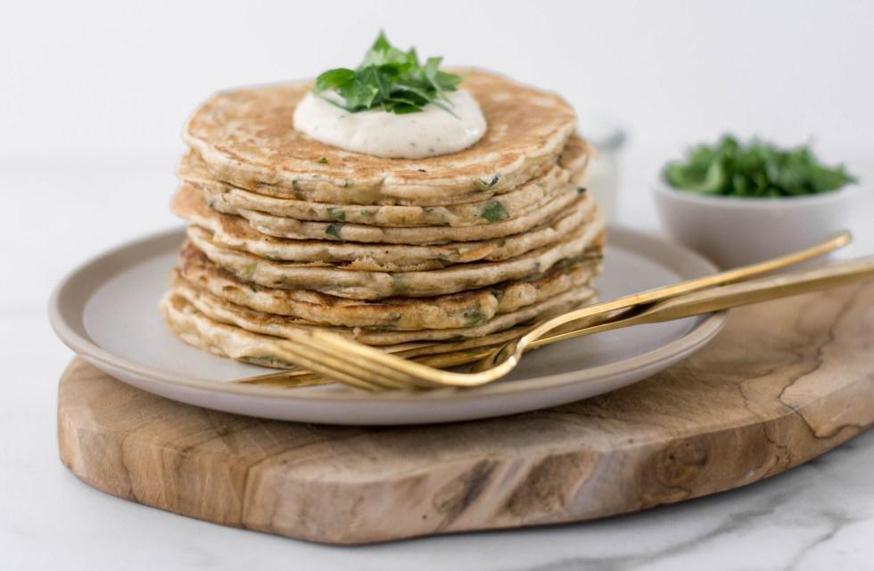Auf diesem Bild sind vegane Zucchini Pfannkuchen zu sehen, die von vorne fotografiert wurden. Die Pfannkuchen wurden auf einem Teller gestapelt und davor liegt goldenes Besteck. Im Hintergrund steht eine Schale mit geschnittener Petersilie.