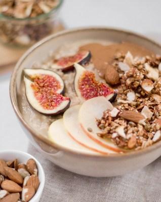 Hier ist ein zuckerfreies Apfel - Zimt Granola zu sehen, welches auf einem Porridge mit frischen Feigen und Äpfeln angerichtet wurde.