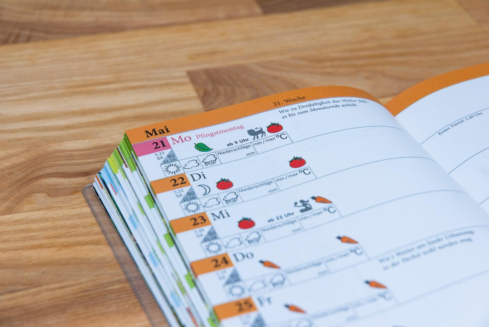 Das Gartenjahrbuch von kraut & rüben liegt auf einem Tisch, aufgeschlagen im Mai.