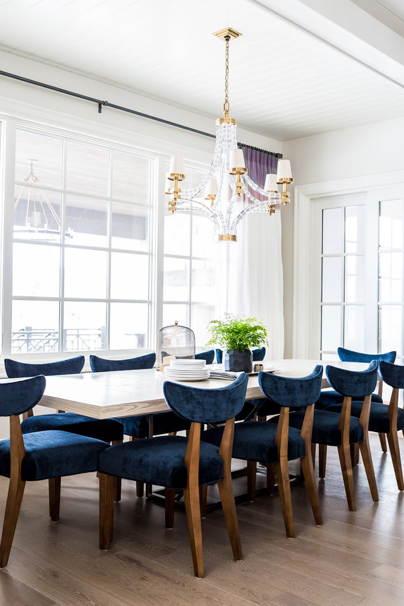 Dining room with glass beaded chandelier and blue velvet dining room chairs