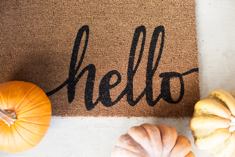 FALL PORCH DECOR WITH WALMART by popular interior designers blog, E. Interiors: image a front porch decorated with a hello door mat and pumpkins from Walmart.