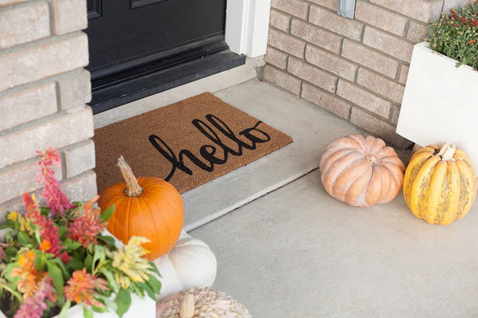 FALL PORCH DECOR WITH WALMART by popular interior designers blog, E. Interiors: image a front porch decorated with a Fall wreath, hello door mat, pumpkins and Mums from Walmart.