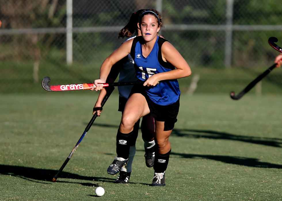 woman wearing blue and black jersey holding field hockey