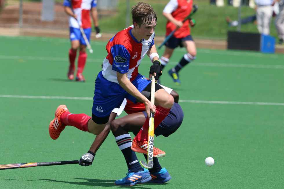 man in red and blue jersey shirt playing hockey