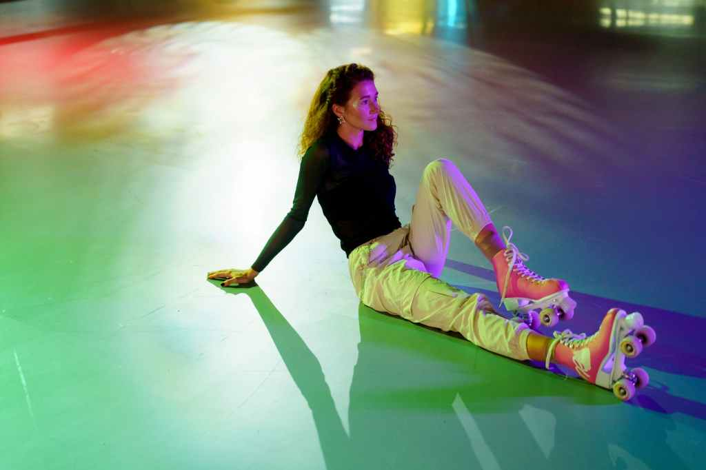 woman in black long sleeve shirt and pink pants lying on floor