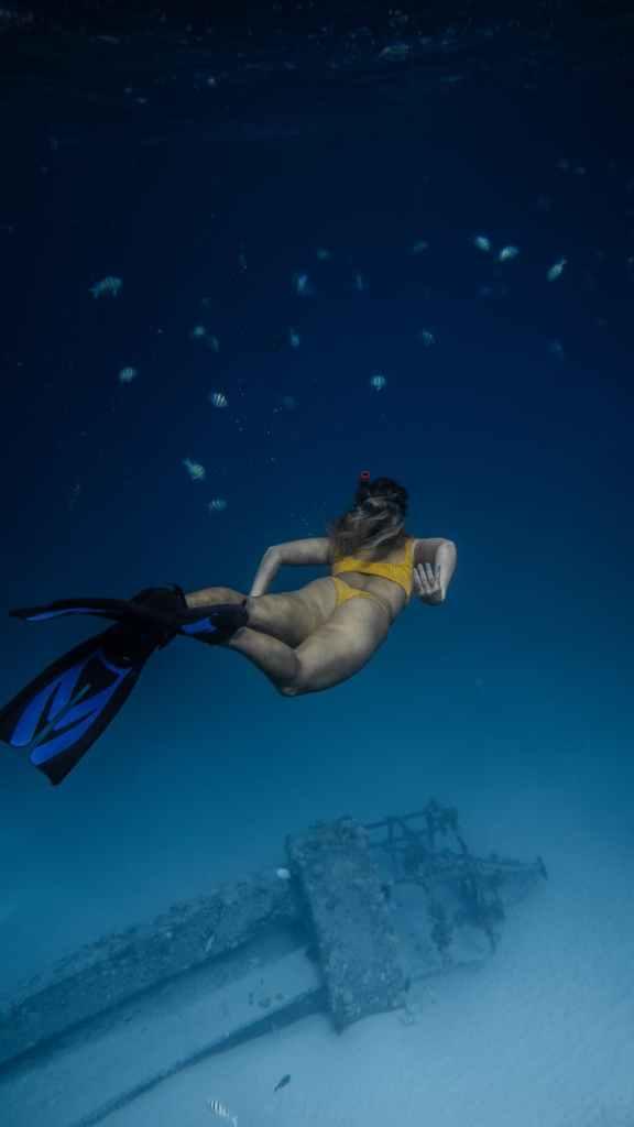 unrecognizable woman exploring ruins underwater