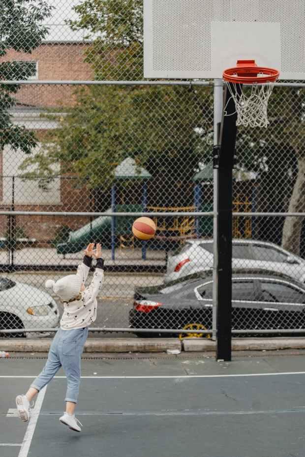 anonymous girl playing basketball on playground